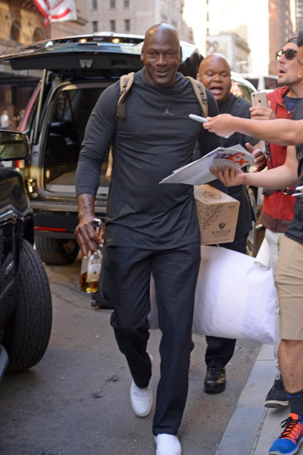 Michael Jordan carries half empty bottle of Tequila and a pillow as he checks out of New York hotel photo