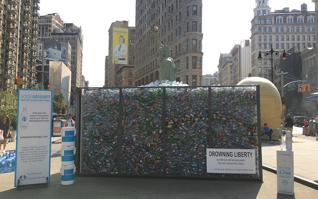 Sodastream Behind Ny Lady Liberty Replica Drowning In Plastic Bottles photo