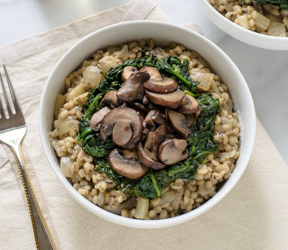 Bowl Of Creamy Barley Risotto With Mushrooms And Spinach photo